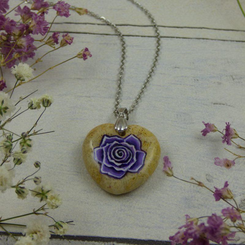 Rose violette peinte sur une pierre naturelle, une corail fossil