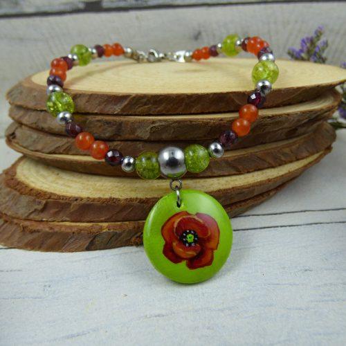 un bracelet avec une fleur de coquelicot
