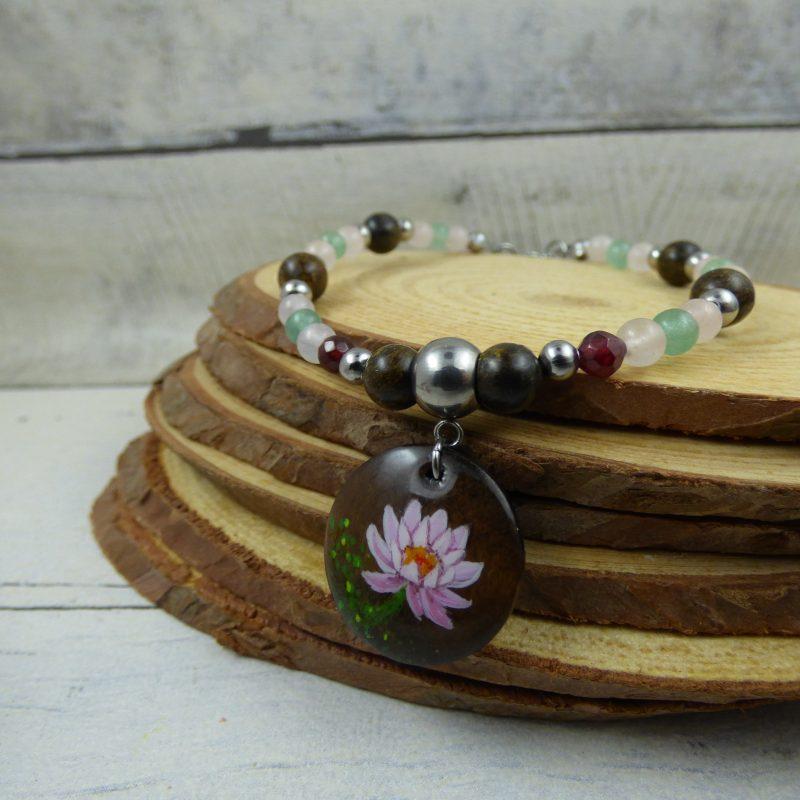 un bracelet avec une fleur de lotus peinte à la main