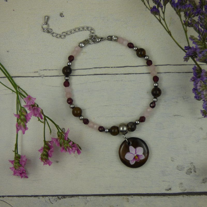un bracelet avec une fleur d'orchidee peinte à la main