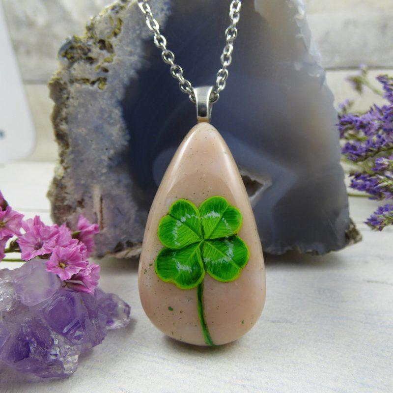 un bijou avec un trefle a quartre feuilles peint à la main
