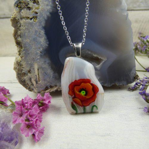 une fleur de coquelicot peinte à la main sur une pierre
