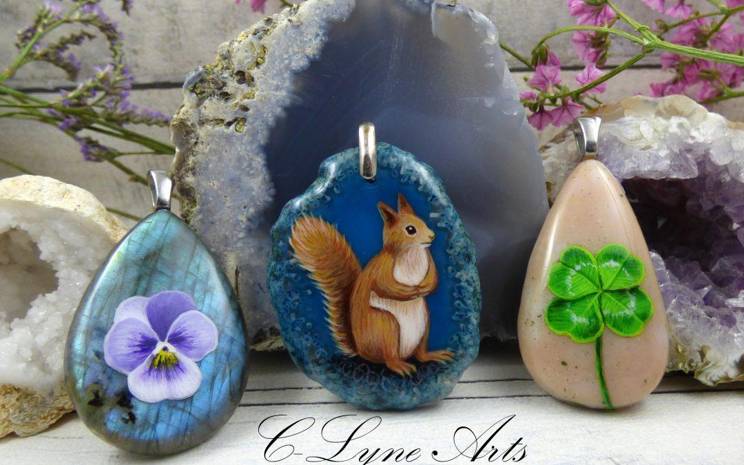 pendentif en pierre avec peinture de fleur, ecureuil et trefle