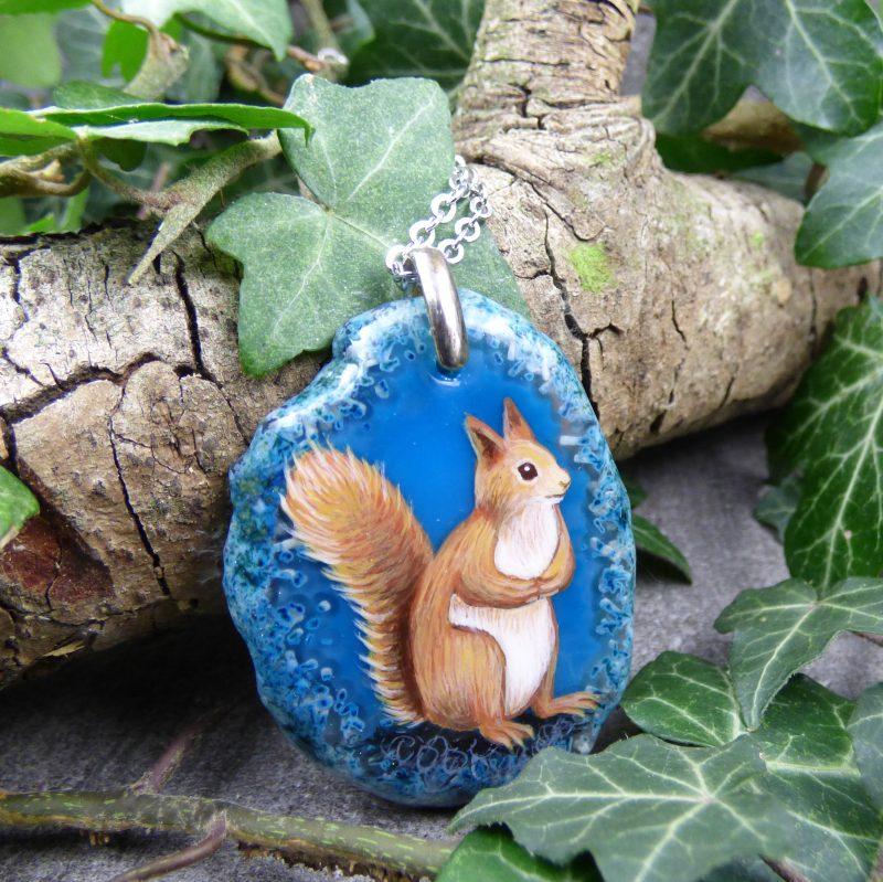 bijou avec un ecureuil peint sur une pierre bleue