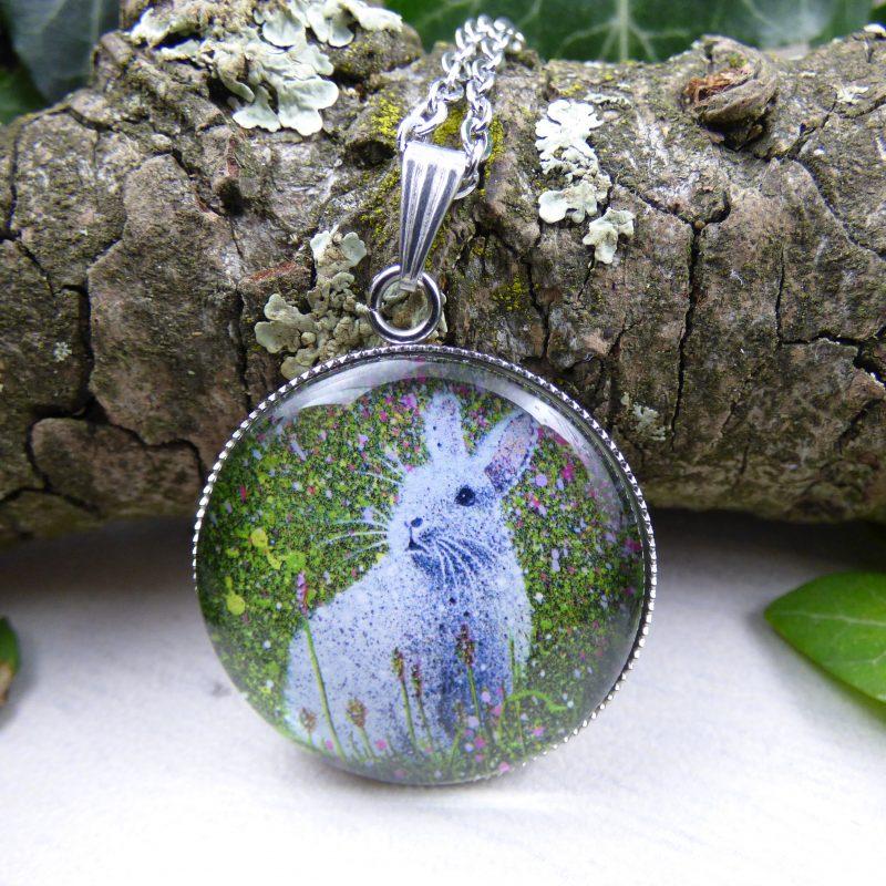 pendentif avec la photo d'un lapin blanc dans l'herbe