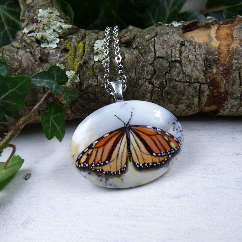 pendentif avec un papillon sur une pierre d'opale blanche