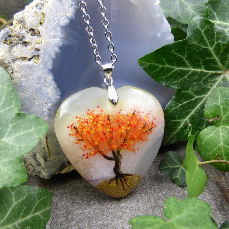 pendentif avec arbre peint sur une pierre en forme de coeur