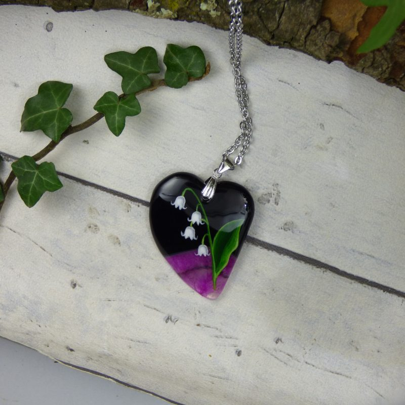 muguet peint à la main sur une pierre en forme de coeur