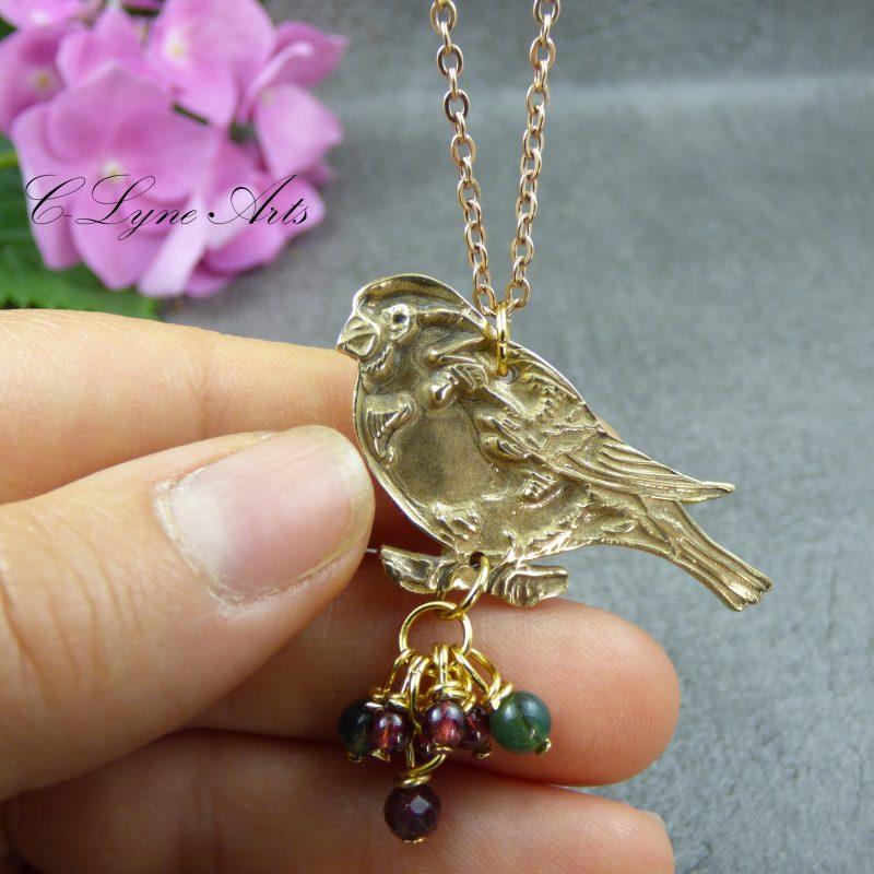 pendentif avec un oiseau en bronze avec des perles