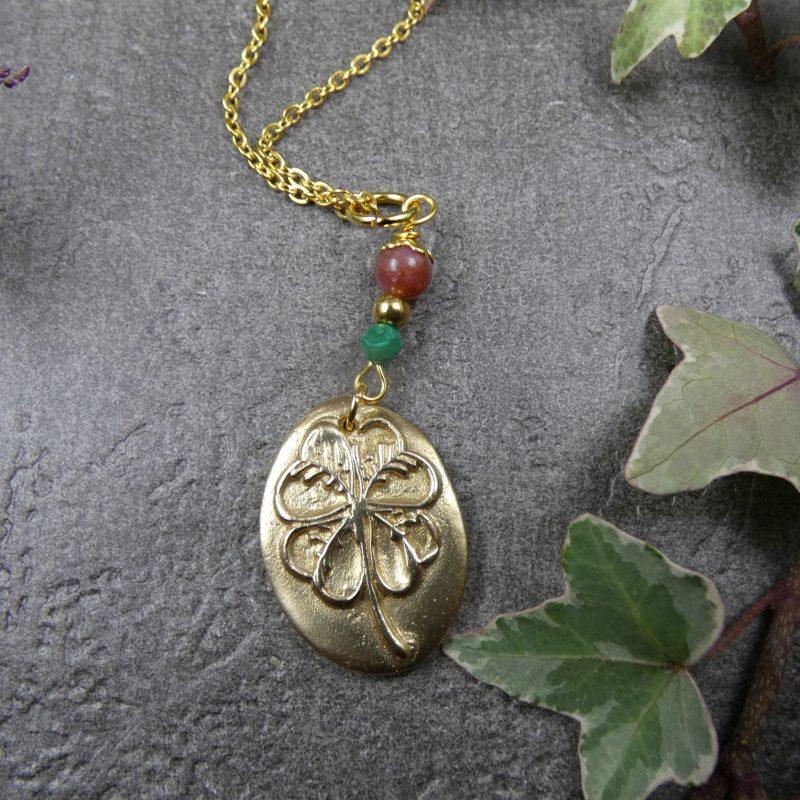 pendentif avec médaillon doré avec un trefle a quatre feuilles