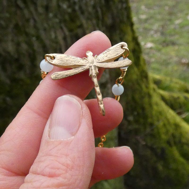 bijou feerique avec un libellule dorée posée sur la main