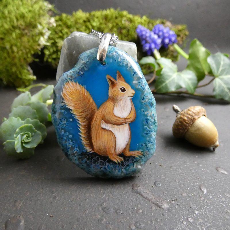 pendentif artisanal avec un écureuil peint sur une pierre