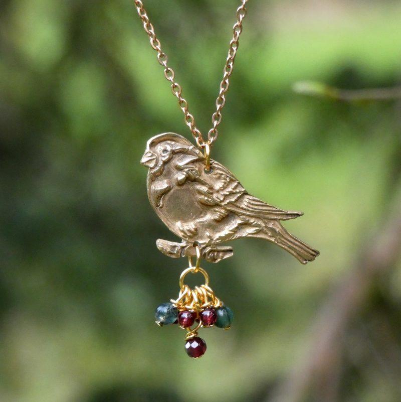 bijou avec un oiseau en bronze doré et petites pierres