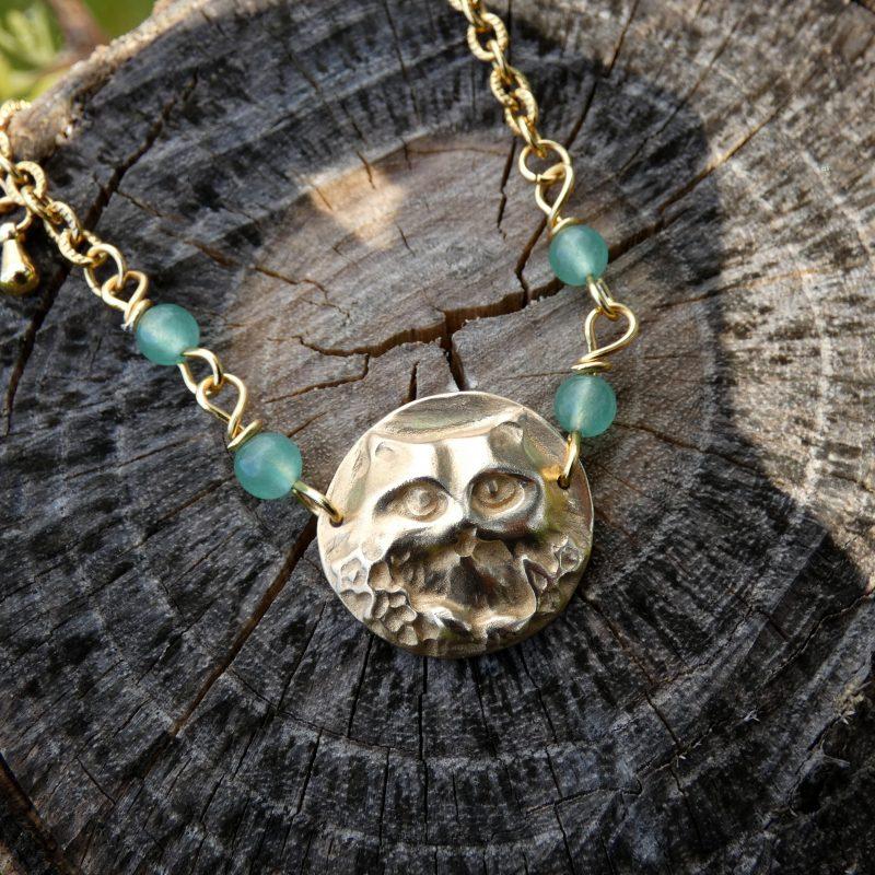bracelet en pierre naturelle avec une tete de chat sur un tronc d'arbre