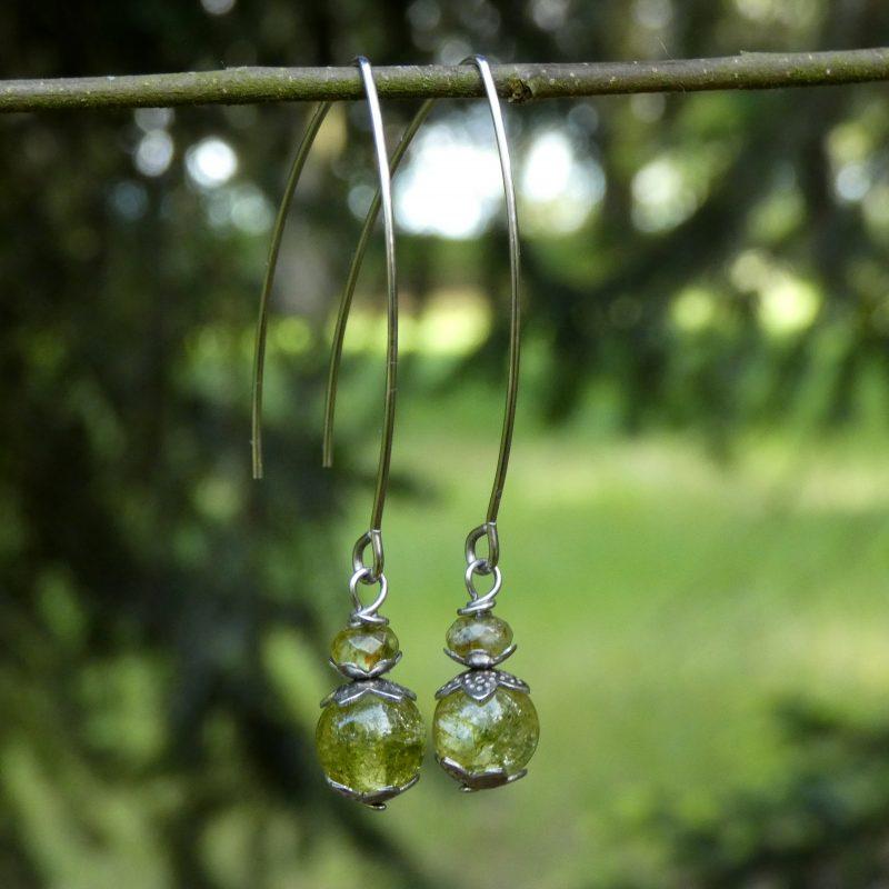boucles d'oreilles en pierres de péridot sur une branche
