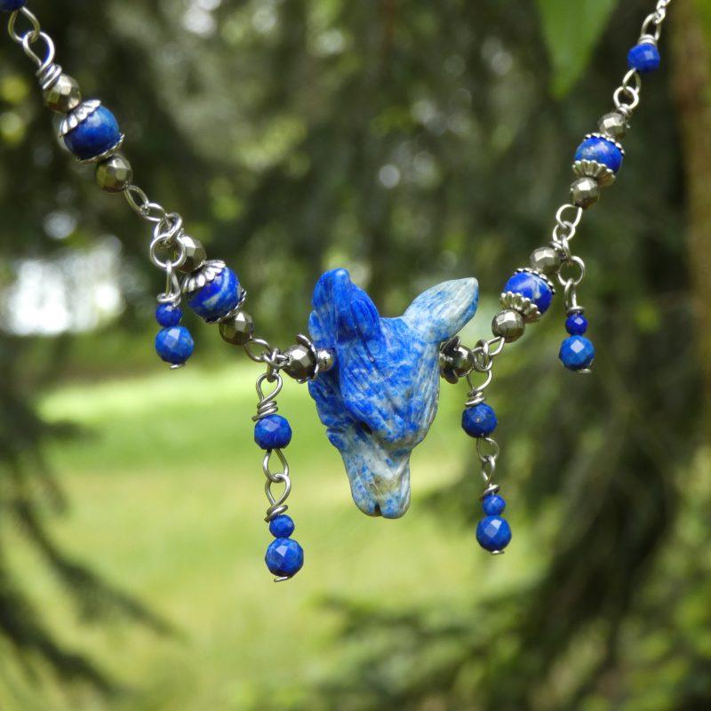 bijou avec perle et tête de loup sculptée dans une pierre
