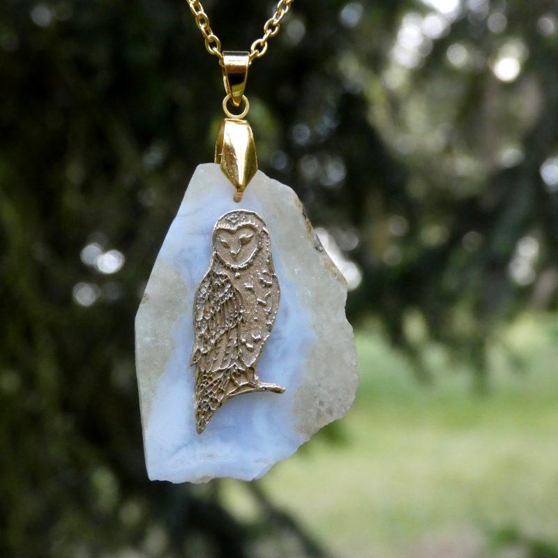 pendentif avec une chouette dorée sur une pierre d'agate bleue